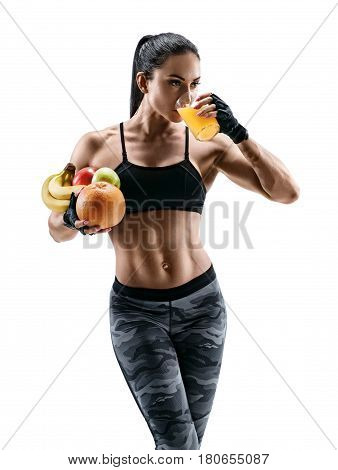 Resting time. Attractive young woman in sports wear hold fresh fruits and drink orange juice. Organic food and health concept.