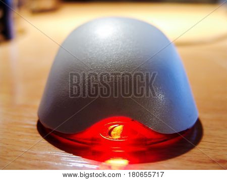 Computer mouse on a table with a red glowing diode. Front view