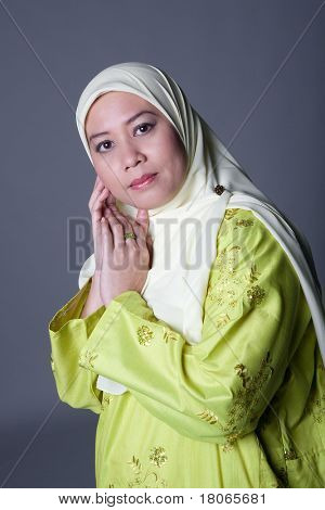 Beautiful Muslim woman in traditional Malay clothing and scarf poster