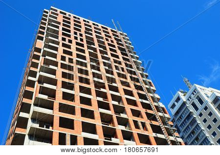 Panoramic and perspective wide angle view to high-rise building under construction exterior. The site building construction facade walls against blue sky.