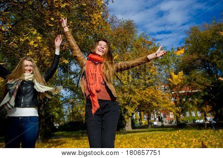 Mellow autumn. Two girls are students cheerfully spend time in the city park. Good weather blue sky. Girlfriends throw armfuls of dry yellow leaves up and rejoice as children.