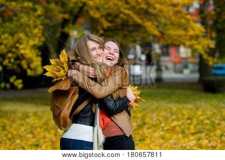 Two nice girls joyfully embrace in the autumn park. They rejoice to a meeting and beauty of the autumn nature. In hands at girlfriends bouquets of autumn leaves.