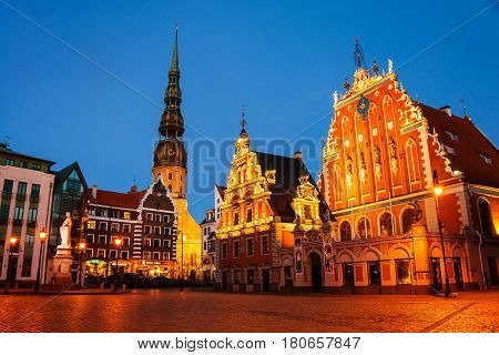 Riga, Latvia. Illuminated House of the Blackheads and Cathedral in the old town of Riga, Latvia. Town square at night. Sunset sky