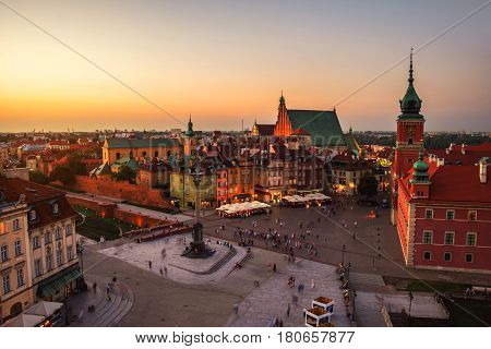 Warsaw, Poland. Nightlife in Warsaw, Poland, people at the palace square. Illuminated historical buildings at night. Sunset with colorful sky.
