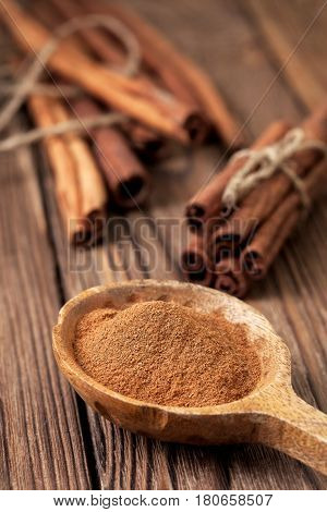 Ground cinnamon in a wooden spoon cinnamon sticks on an old wooden background
