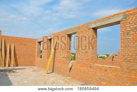 Interior of a Unfinished Red Brick House Walls under Construction without Roofing. Closeup on Attic Windows Hole Frame Construction. Attic construction. Unfinished house.