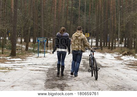 Bike path and bicyclists in the forest in early spring