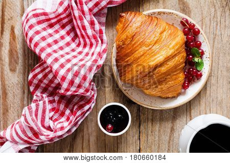 Continental breakfast, table top view food: croissant, jam, berries and coffee on rustic wooden table.