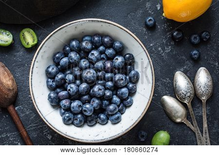 Blueberries and vintage spoons: Top view of fresh blueberries in white ceramic bowl with baby kiwi fruit, lemon and vintage tea spoons on dark stone table. Healthy vegan fresh food concept