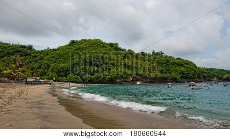 Crystal Bay Nusa Penida Indonesia - March 9 2017: Local people rest on the beach and swim.