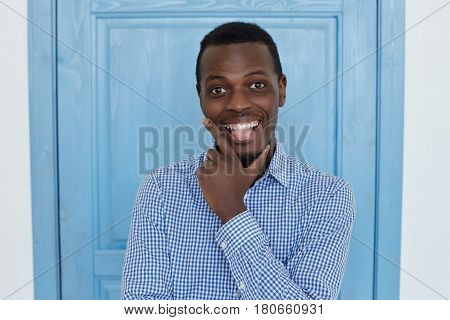 Young and handsome dark-skinned man having fun grimacing at office break indoor looking and showing tongue at the camera. People and lifestyle concept.