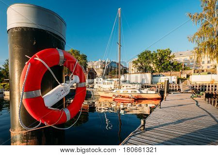 Riga, Latvia - July 1, 2016: Lifebuoy Hanging On A Pole Near City Pier Harbour Bay And Quay In Summer Sunny Evening.