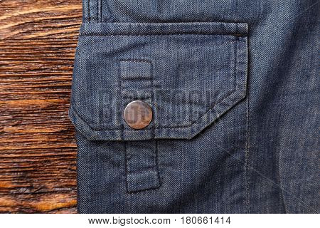 Background pocket of men's pants made of natural fabric on a wooden background. Horizontal photo