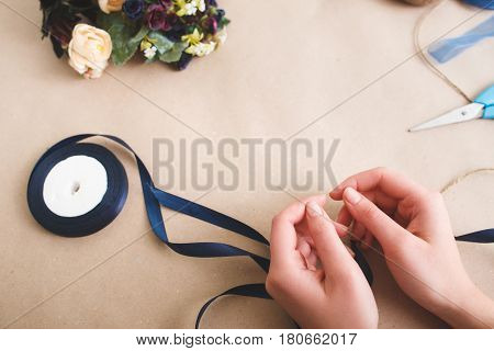 Florist workplace, hands with colorful artificial flowers and ribbons on beige background, top view. Creative art, beautiful decoration, craftsmanship concept.