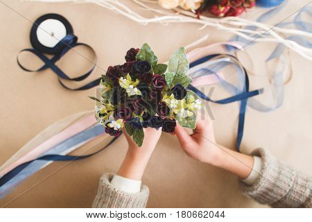 Unrecognizable woman hold creative colorful bouquet from artificial flowers, flat lay. Making beautiful decorations, handmade art, craftsmanship, handiwork concept.