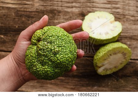 Woman showing green tropical fruit flat lay. Top view on female hand holding full osage orange, two cut halves of Adam's apple on wooden table. Exotic, alternative medicine, pharmacology concept