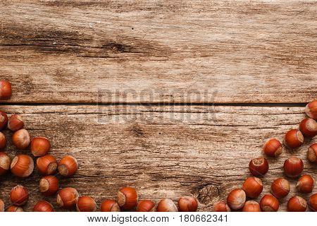 Wooden background with hazelnuts border free space. Rustic backdrop with brown filbert nuts on old wood. Harvest, fall, food ingredient concept