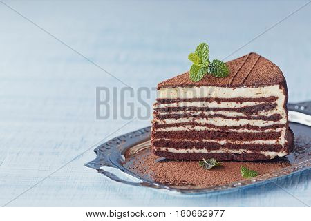 Slice of delicious chocolate cake on silver plate with fresh mint on light blue wooden table background. Space for text.