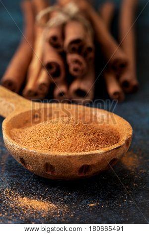 Ground cinnamon in a wooden spoon cinnamon sticks on blue background
