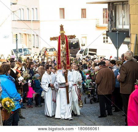 Neuoetting,Germany-April 9,2017: Altar boys walk at the head of the Palm Sunday procession after the blessing of the Pussy Willow flowers