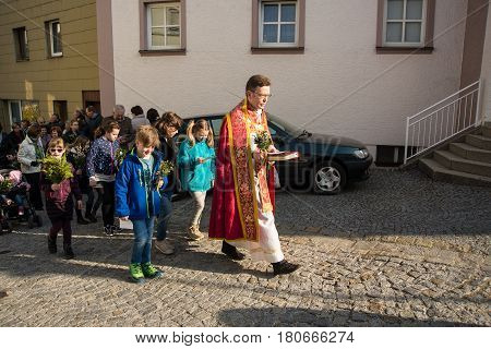 Neuoetting,Germany-April 9,2017: A priest walks during the Palm Sunday procession after the blessing of the Pussy Willow fowers