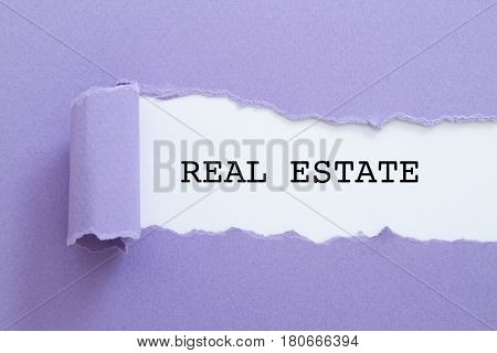 REAL ESTATE word written under torn paper.