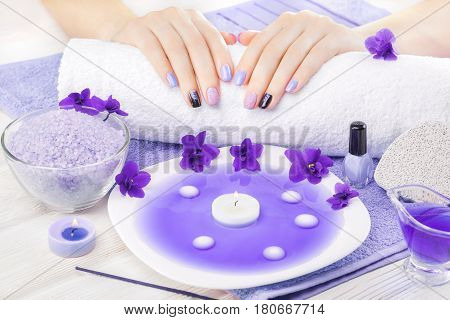 beautiful blue manicure with violet, candle and towel on the white wooden table. spa