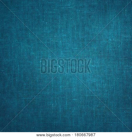 Coarse Blue Canvas Fabric Cloth Burlap Sack texture with darkened edges. Rough grunge background or wallpaper close up. Web banner Square Image