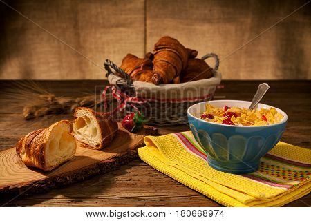 Continental breakfast with cornflakes and strawberries in a cup of milk on a yellow napkin and croissant