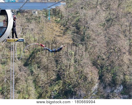 Sochi - April 4 2017: A very brave man jumping from the world's longest pedestrian bridge in the Akhshtyr gorge April 4 2017 Sochi Russia