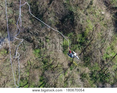 Sochi - April 4 2017: A man with a rubber rope jumping from the world's longest pedestrian bridge in the Akhshtyr Gorge April 4 2017 Sochi Russia