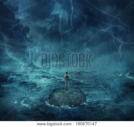 Lost man standing abandoned on a rock island in middle of the ocean in a stormy night with lightnings in the sky. Looking for help trying to survive. Adventure journey and hard determination concept.
