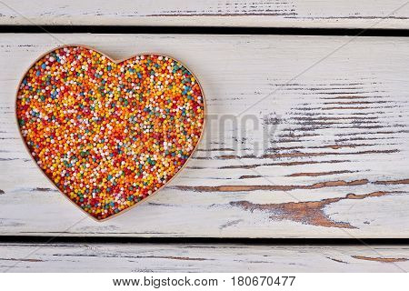 Heart shaped box, sprinkle dots. Bright sugar sprinkles, wood background. Valentine gift design.