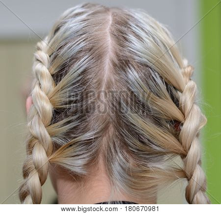 Blonde has braided long hair to a plait