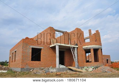 New Building Brick House Construction with Doorway Columns and Windows frame Exterior. Building Site Outside. Unfinished house.