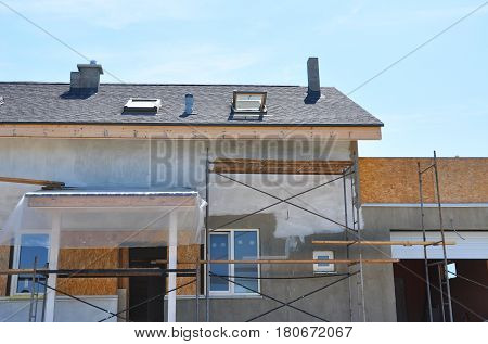 Construction or repair of the rural house with skylights ventilation eaves windows garage doorway, roofing fixing facade insulation plastering and using color. Unfinished house. Painting wall. Stucco wall. Asphalt Shingles Roof. poster