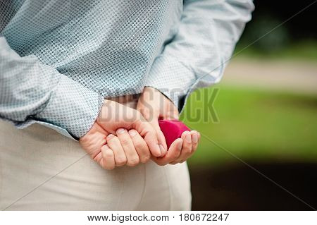 Male hands holding ring in red box, man makes proposal woman