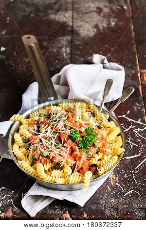 Fusilli pasta dish with tuna fish, tomato sauce, capers, black olives and parmesan cheese in a cooking pan on a wooden table, selective focus