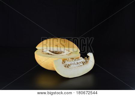Melon and a slice of melon on a black background
