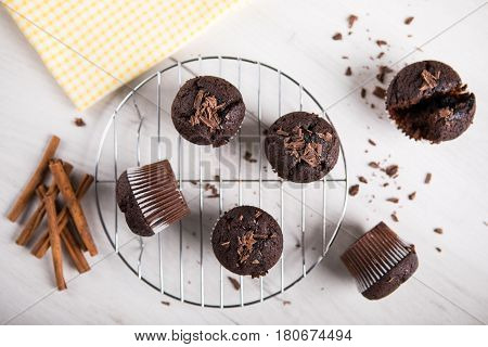 Tasteful Chocolate muffins on white wooden table.