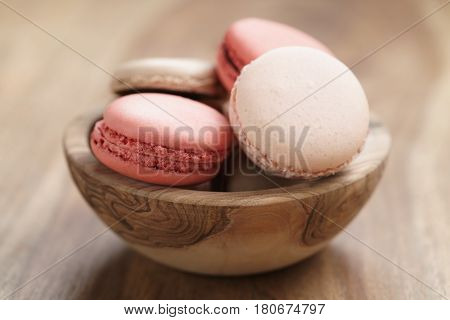 pastel colored macarons with strawberry, rose and caramel flavour in wood bowl on table