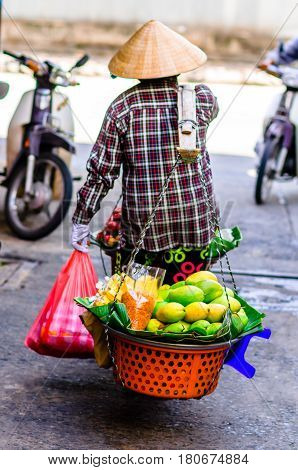 View on Vietnamese market trader balance food in Hanoi