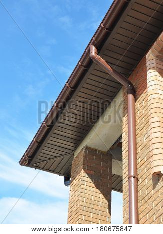 New Rain Gutter Drain Pipe Downspout Installation on the Unfinished House Facade Brick Wall Outdoor. Install Drainage System with Plastic Siding Soffits and Eaves Exterior.