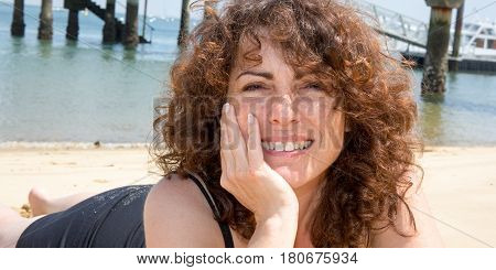 A Brunette Forties Woman In A Black Dress Lying On The Beach