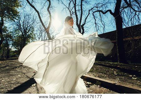 Autumn sun shines behind a whirling bride