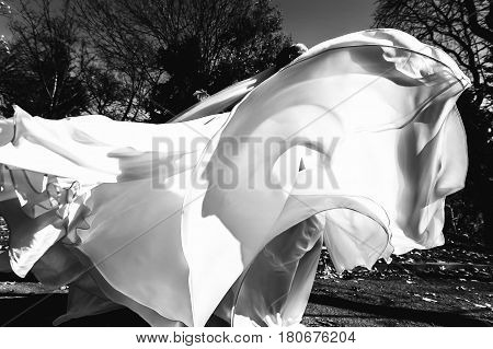 The waves of a whirling dress behind which stands a bride