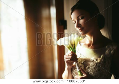 Bride holds a tender bouquet of callas behind her face