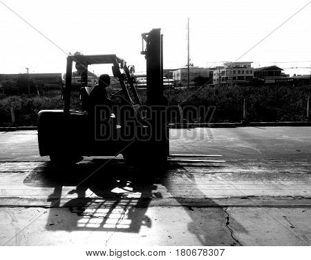 Detail worker on forklift wait for lift out cargo on struck by black and white photography