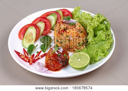 Thai food Fried jasmine rice with canned fishmackerel in tomato sauce topped halve green lemonsliced tomatocucumberred chilired onionlettuce and kaffir lime leaves served on brown leather pad.