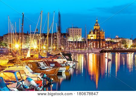Scenic summer evening panorama of the Old Port pier architecture with tall historical sailing ships yachts and boats and Uspenski Orthodox Cathedral in the Old Town in Helsinki Finland